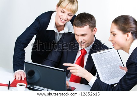 Portrait of confident partners looking at laptop screen together with smiles