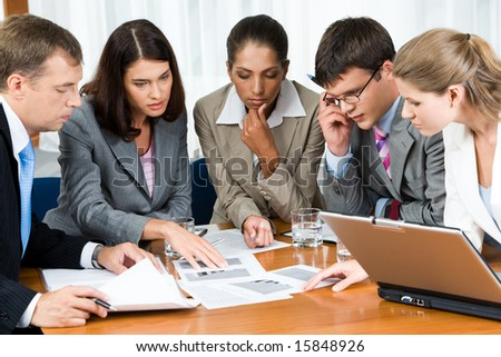Portrait of confident people looking seriously at business papers during working meeting