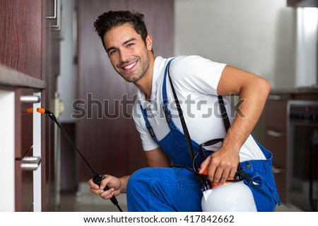 Portrait of confident pesticide worker crouching with sprayer at home