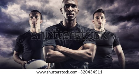 Portrait of confident rugby player with arms crossed against blue sky with white clouds #320434511