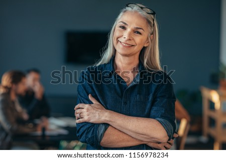Portrait of confident senior business woman standing in office with her arms crossed. Mature female in office with colleagues discussing work at the back.