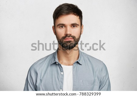 Portrait of confident serious male model has black beard and mustache, dressed in casual denim shirt, looks seriously into camera, isolated over white background. Hipster guy models in white studio