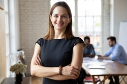 Portrait of confident smiling attractive female team leader in formal dress standing in modern workplace. Happy young 30s businesswoman boss employer partner posing indoors, looking at camera.
