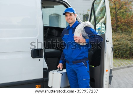 Portrait of confident technician with cable coil and toolbox standing outside van