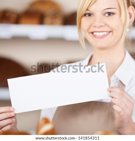 Portrait of confident waitress holding blank sign in cafe