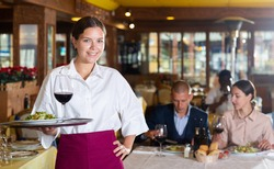 Portrait of confident waitress ready to serving meals to guests in restaurant