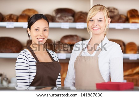 Portrait of confident waitresses standing together at cafe counter