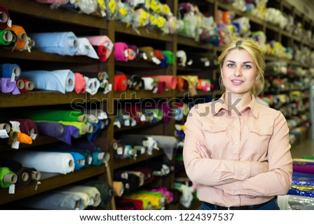 Portrait of confident woman administrator of tissue store near shelves with multicolored fabrics #1224397537
