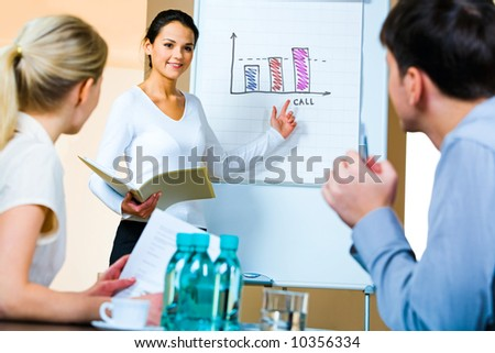 Portrait of confident woman demonstrating her project pointing to the whiteboard