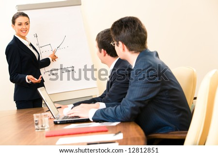 Portrait of confident woman demonstrating her report to colleagues