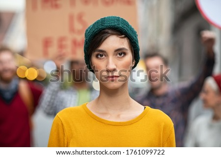 Portrait of confident woman in march fighting for freedom. Young latin woman empowerment strike on street. Casual girl in march to protest on equality rights.