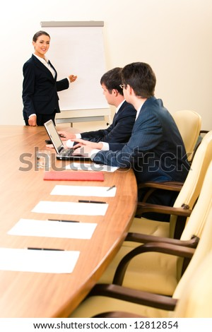 Portrait of confident woman teaching a lecture to business people pointing at white board
