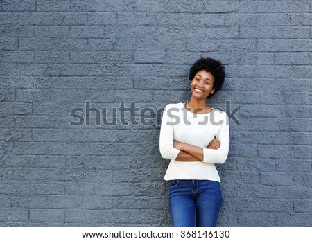 Portrait of confident young african woman standing against a gray wall