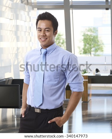 Portrait of confident young asian businessman at office.