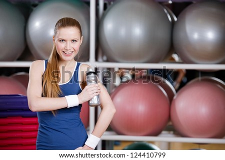 Portrait of confident young athlete woman in sportswear holding a water bottle in gym