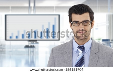 Portrait of confident young businessman at office with financial graph on TV.
