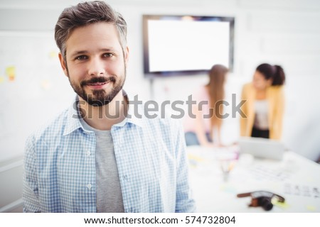 Portrait of confident young businessman standing in meeting room at creative office