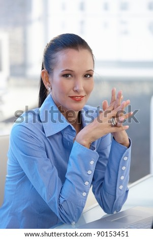 Portrait of confident young businesswoman smiling at camera with fingers folded.?