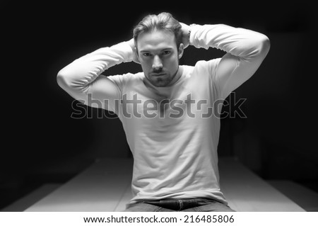 Portrait of confident young man wearing white shirt against black background. Black and white image.