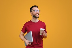 Portrait of confident young smiling bearded man in casual red t-shity and trendy spectacles holding laptop and paper cup of coffee, isolated on yellow background.