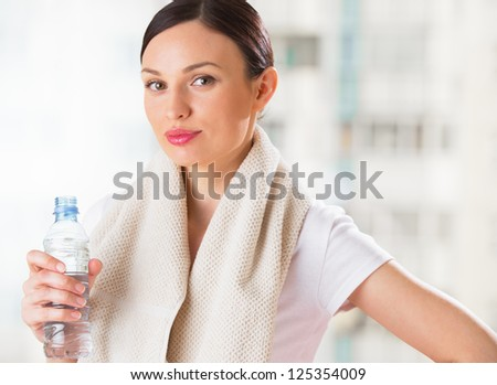 Portrait of confident young woman in sportswear holding a water bottle in gym