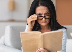 Portrait of confused senior woman squinting to see more clearly, wearing and touching eyeglasses, trying to read paper book, having difficulties seeing text because of bad vision problems and issues