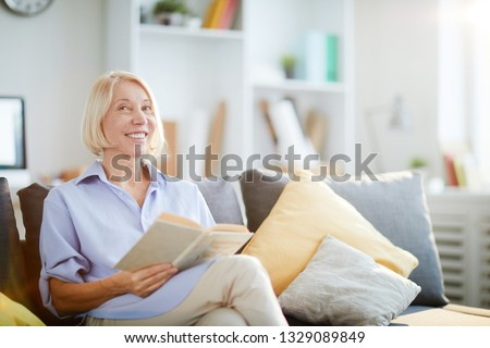 Portrait of contemporary adult woman smiling happily sitting on sofa at home and looking at camera, copy space