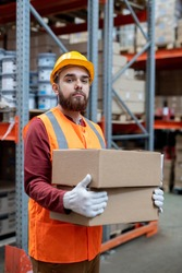 Portrait of content confident young depository mover in hardhat and reflective vest standing with boxes against warehouse frame