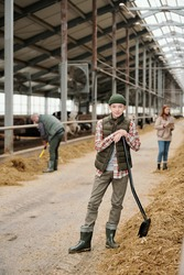Portrait of content teenage boy in hat standing with shovel in cowshed, he working with parents at farm