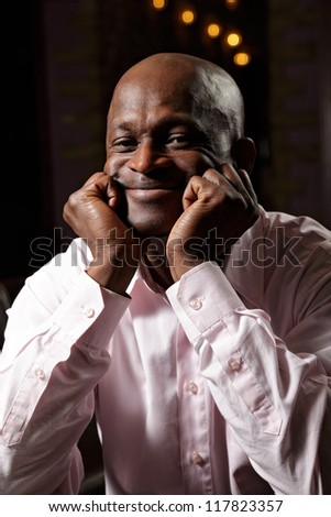 Portrait of contented african man in pink shirt leaning on fists