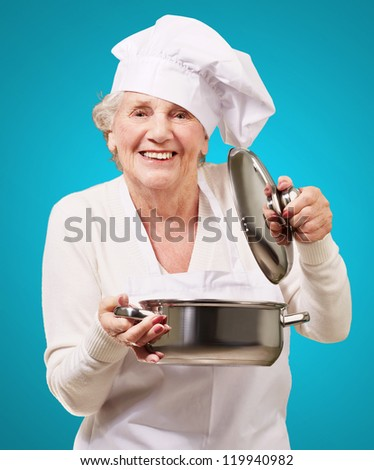 portrait of cook senior woman opening sauce pan over blue
