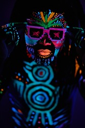 portrait of cool african man with fluorescent body art dancing isolated in dark space. dj man perform dance, mysterious dancer with colorful prints on face and body