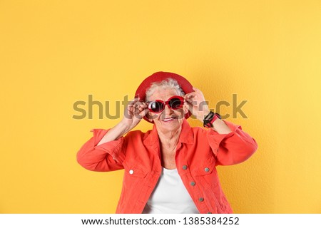 Portrait of cool grandmother on color background #1385384252