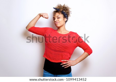 Portrait of cool young black woman flexing bicep muscle