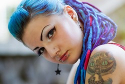 Portrait of cool young girl with blue braided hair.Lip piercing on face,big tattoo on shoulder.Punk white teenager female with body modification.Bizarre youth fashion.Cool hair model with braids