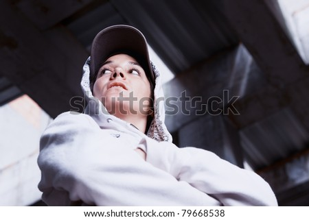 Portrait of cool young girl with cap and white hoody pullover in factory hall.