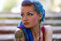 Portrait of cool young tattooed punk chick with long dyed braided hair.Stylish teenager girl with tatoo on shoulder posing outdoor.Attractive street fashion model