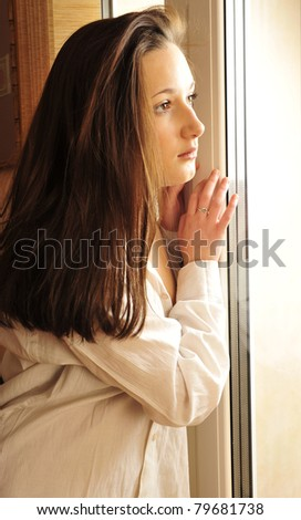 Portrait of cosy young girl standing near a window at home