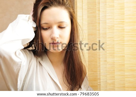 Portrait of cosy young girl standing near a window at home.