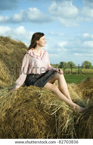 Portrait of country girl on hay in summer