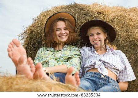 Portrait of country girls on hay in summer