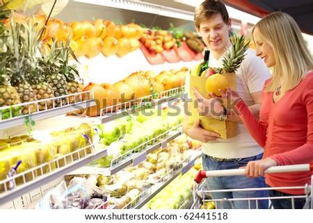 Portrait of couple choosing fruits in supermarket