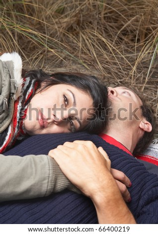 Portrait of couple laying down in beach grass