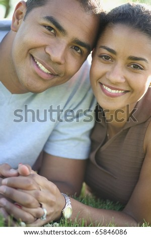 Portrait of couple laying in grass