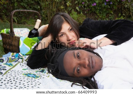 Portrait of couple laying on blanket with picnic basket