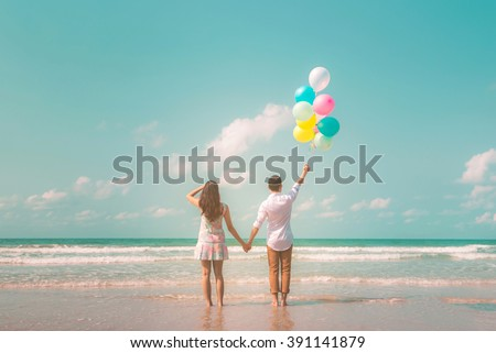 Portrait of couple of young happy married hipsters in trendy vintage clothes standing together on the beach with balloons. Sunny summer day. Pastel colors tone