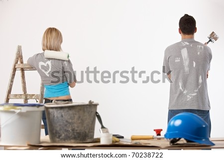 Portrait of couple painting at home, holding paint roller and brush, looking at wall.?