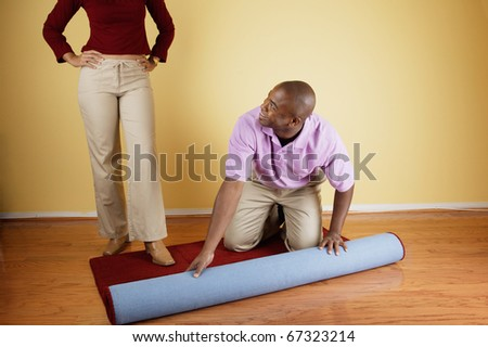 Portrait of couple rolling out carpet