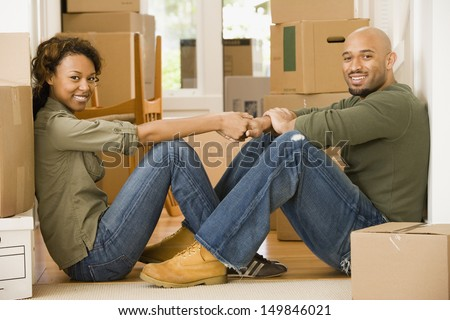 Portrait of couple sitting in new house