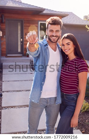 Portrait Of Couple Standing Outdoors In Front Of House With For Sale Sign In Garden Holding Keys Foto stock ©